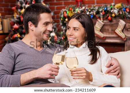 Happy New Year! Beautiful young loving couple bonding to each other and holding wine glasses with Christmas Tree in the background  - stock photo