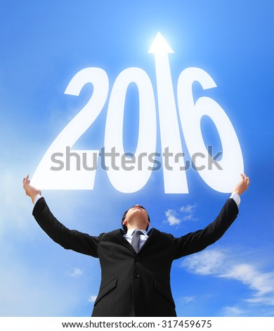 Happy new year - Business man holding 2016 new year imagination with sky and cloud, asian