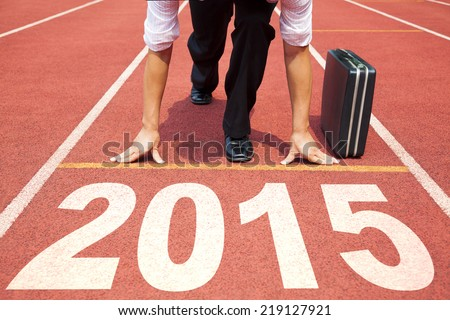 happy new year 2015. businessman preparing for running with briefcase - stock photo