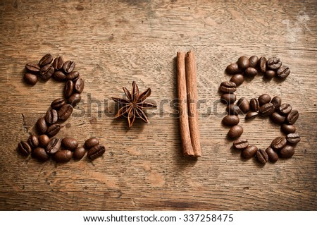 Happy new year card 2016 with coffee beans,  anise and cinnamon on wooden background - stock photo