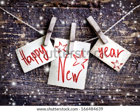 Happy New Year card with  snow on wooden background - stock photo