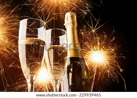 Happy new year, champagne with sparklers on dark background - stock photo