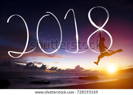 happy new year concept.young man jumping and drawing 2018