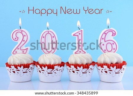 Happy New Year cupcakes with lit 2016 candles on white table against a blue background, with sample greeting text.  - stock photo