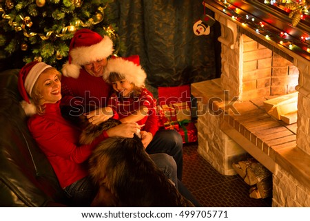 Happy New Year. Family playing with dog in Christmas festive decorated living room. Pet, people, holiday concept
