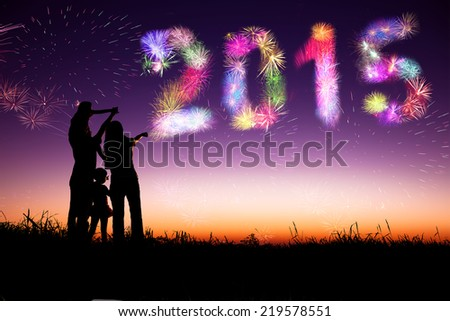 happy new year 2015.family standing on the hill and watching the fireworks - stock photo
