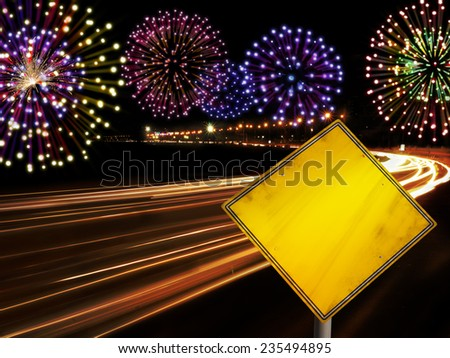 Happy New Year fireworks and city cars highway lights with copy space in yellow road sign. - stock photo