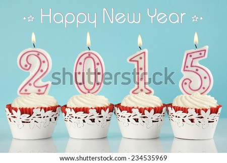 Happy New Year for 2015 red velvet cupcakes in red and white theme with lit candles and pale blue and white background, with sample text. - stock photo
