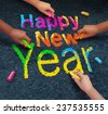 Happy new year friends concept with a group of hands representing ethnic groups of young people holding chalk cooperating together as a diverse group celebrating the future. - stock photo