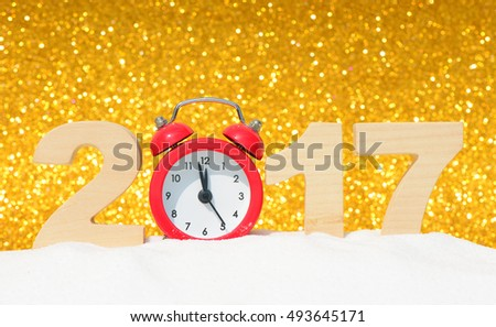 Happy new year 2017 greeting card. Alarm clock and the wooden numbers 2017 in a snowdrift on a gold glitter background