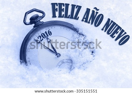 Happy New Year 2016 greeting in Spanish language, Feliz ano nuevo text, pocket watch in snow - stock photo