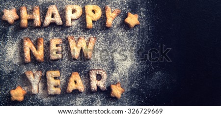 Happy New Year greeting with cookies letters on dark background with blank space  - stock photo