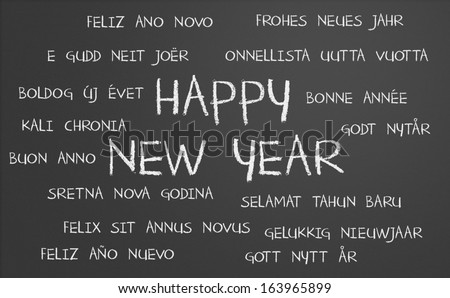Happy new year in many different languages written on a chalkboard - stock photo