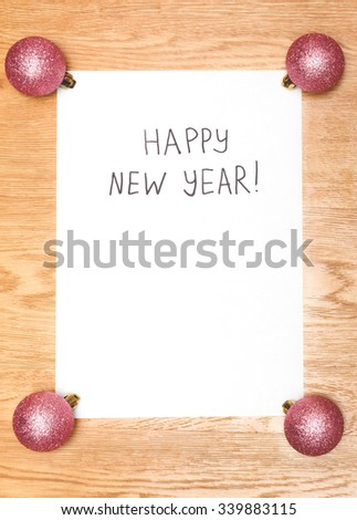 Happy New Year message greeting written on a white paper with new year bright pink balls on wooden background - stock photo
