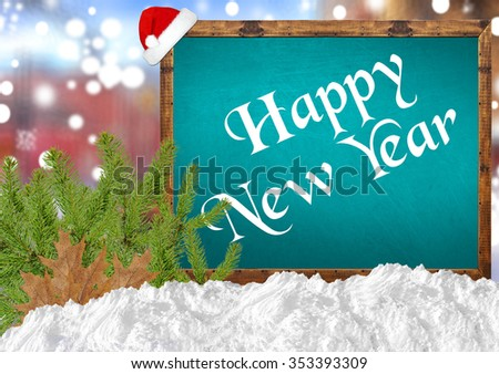 Happy New Year on blue blackboard with blurr city pine and snow
