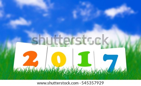 Happy new year 2017 on grass and blue sky background