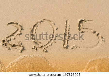 happy new year 2015  on sandy beach with wave