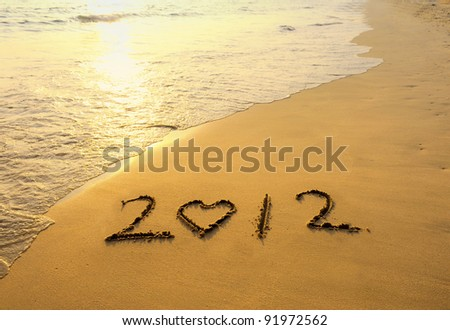 happy new year 2012 on the beach of sunrise - stock photo