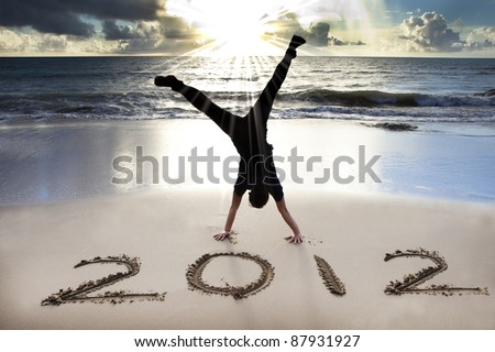 happy new year 2012 on the beach with sunrise background - stock photo
