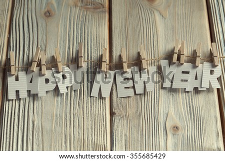 Happy new year - paper letters on wooden background - stock photo