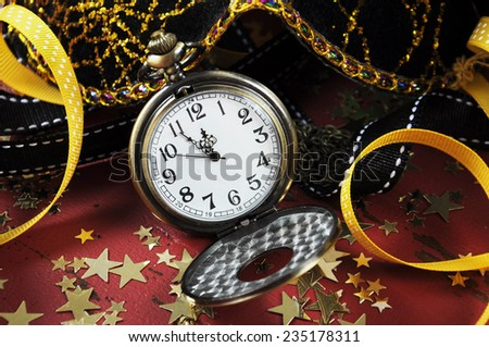 Happy New Year pocket fob watch with five to midnight time and decorations on red rustic distressed vintage wood. - stock photo