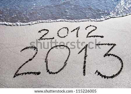 Happy New Year 2013 replace 2012 concept on the sea beach - stock photo