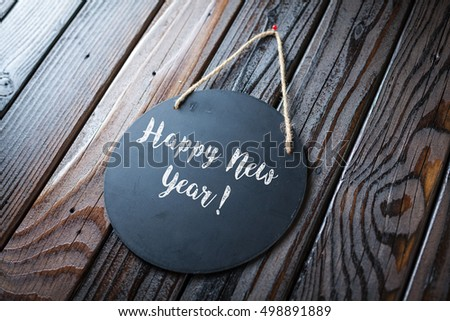 Happy New Year Sign Written In Chalk On Chalkboard On Rustic Vintage Wood Background. Selective Focus.