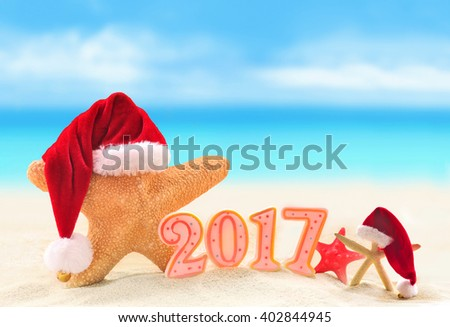 Happy New Year 2017. Starfish in Santa hat on the summer beach.