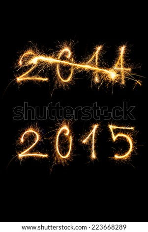 Happy new year 2015. Strike through 2014 digits and 2015 digits made of sparkling light isolated on black background. Old year going, new year comming. - stock photo