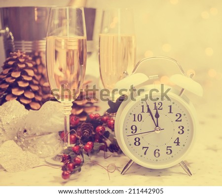 Happy New Year table setting with white retro clock showing five to midnight with champagne and festive decorations against white starry background with bokeh lights, with retro vintage filter.