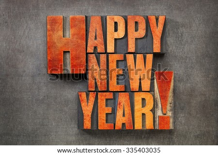 Happy New Year! - text in vintage letterpress wood type blocks stained by red ink on a grunge metal background - stock photo