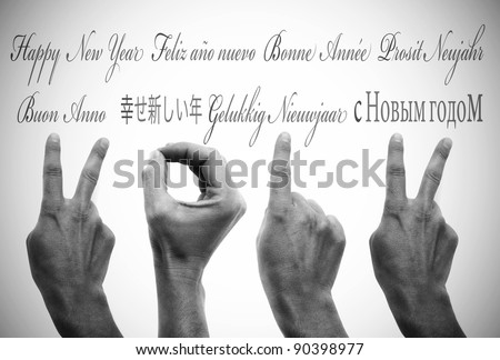 happy new year written in different languages with hands forming number 2012 - stock photo