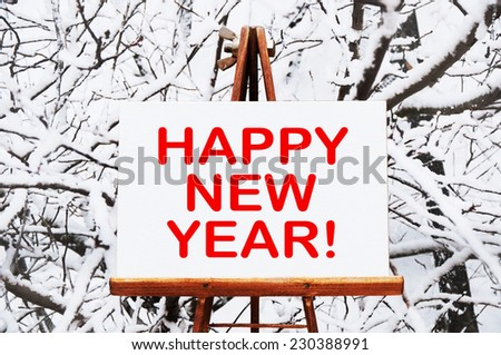 Happy New Year! written on easel with a snow in a background - stock photo