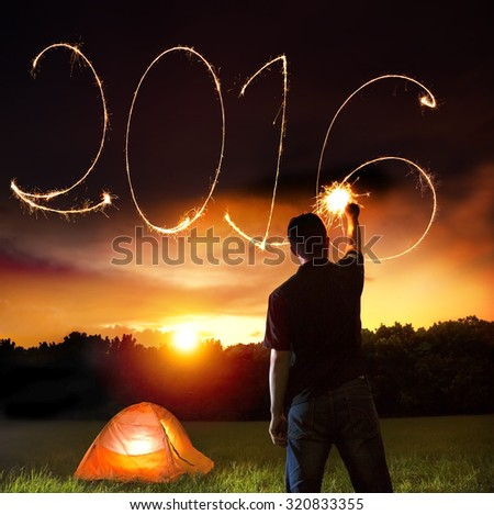 happy new year 2016.young man drawing by sparkler - stock photo