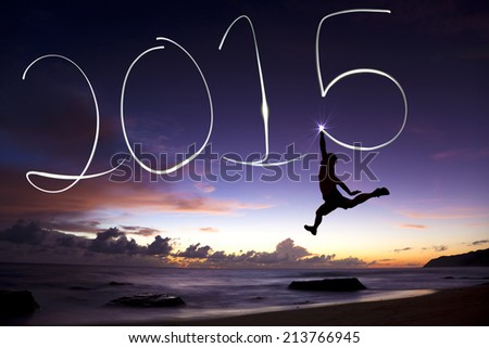 happy new year 2015.young man jumping and drawing 2015 by flashlight - stock photo