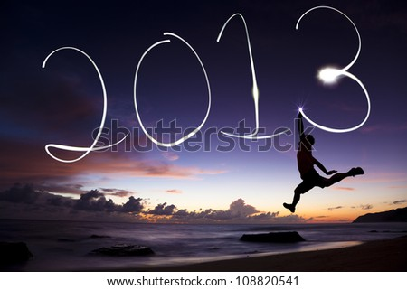 happy new year 2013. young man jumping and drawing 2013 by flashlight in the air on the beach before sunrise - stock photo