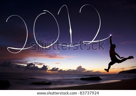 happy new year 2012. young man jumping and drawing 2012 by flashlight in the air on the beach before sunrise - stock photo