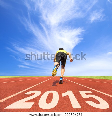 happy new year 2015. young man running on track with blue sky and cloud background - stock photo