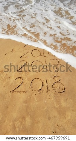 Happy New Years 2017 and 2018 handwritten on sand with a wave coming to erase 2016