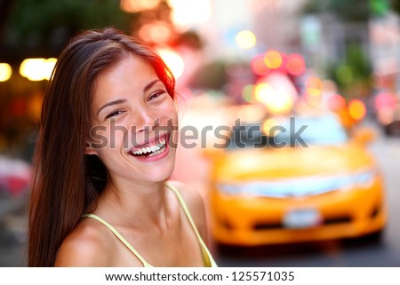 Happy New York City girl. Woman smiling laughing joyful on Manhattan with yellow taxi cab in background. Fresh energetic mixed race Caucasian / Chinese Asian female model smiling candid and real.