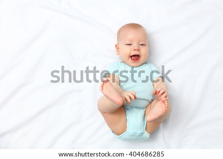 happy newborn baby on the bed at home - stock photo