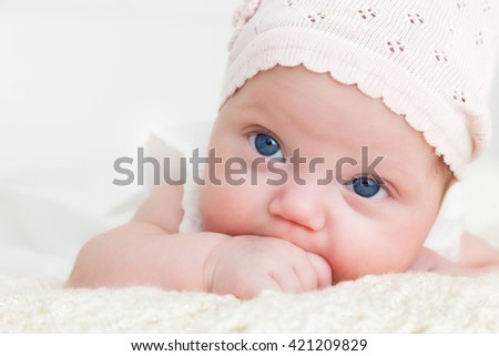 Happy newborn baby portrait, looking at the camera with her blue big eyes. White background.