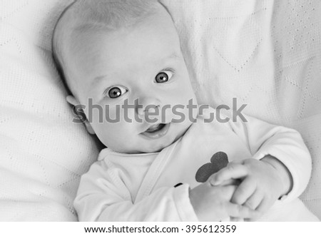 happy newborn baby smiling looking at the camera  ( black and white ) - stock photo