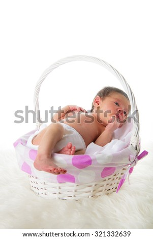 Happy newborn girl sleeping in a basket on a white hair blanket