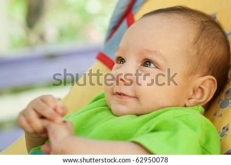 happy newborn lies on a green background - stock photo