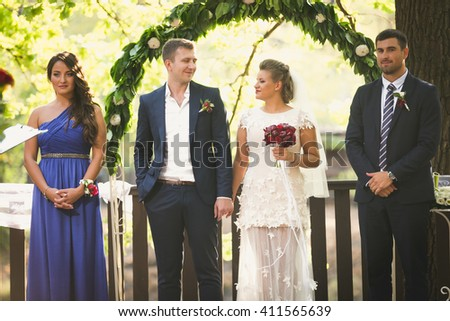Happy newly married couple posing with friends under floral arch - stock photo