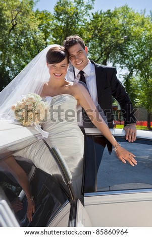 Happy newly wed couple getting in the car - stock photo