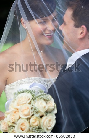 Happy newly wed couple standing together - stock photo