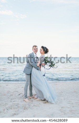 Happy newly-weds having fun by the sea.