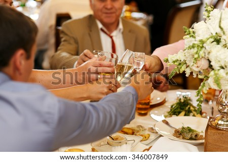 Happy newlywed bride and groom at wedding reception eating and drinking with guests - stock photo